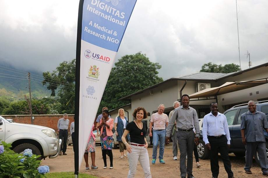 Members of the Dignitas Malawi team walking into the research center compounds smiling at the camera