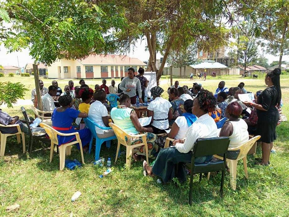 Group of community health workers listening to the instructor on a field on grass