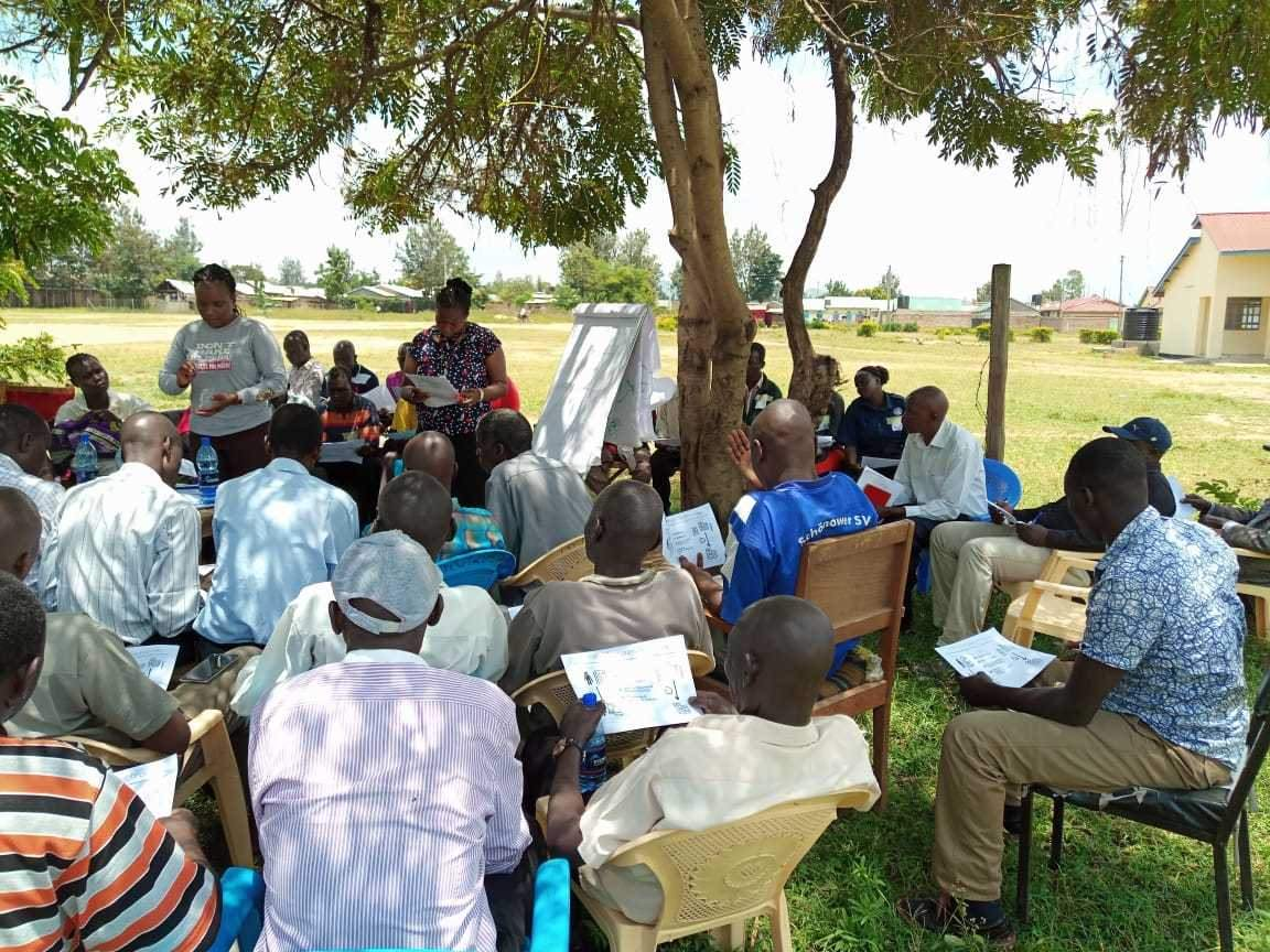 group of participants listening and learning from a Community health worker