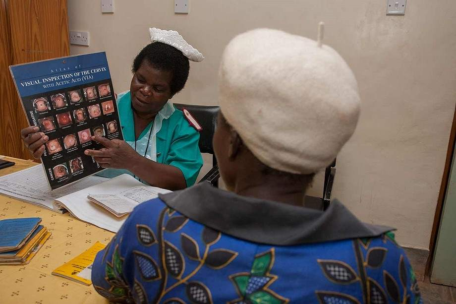 Nurse holds up chart to educate a patient.