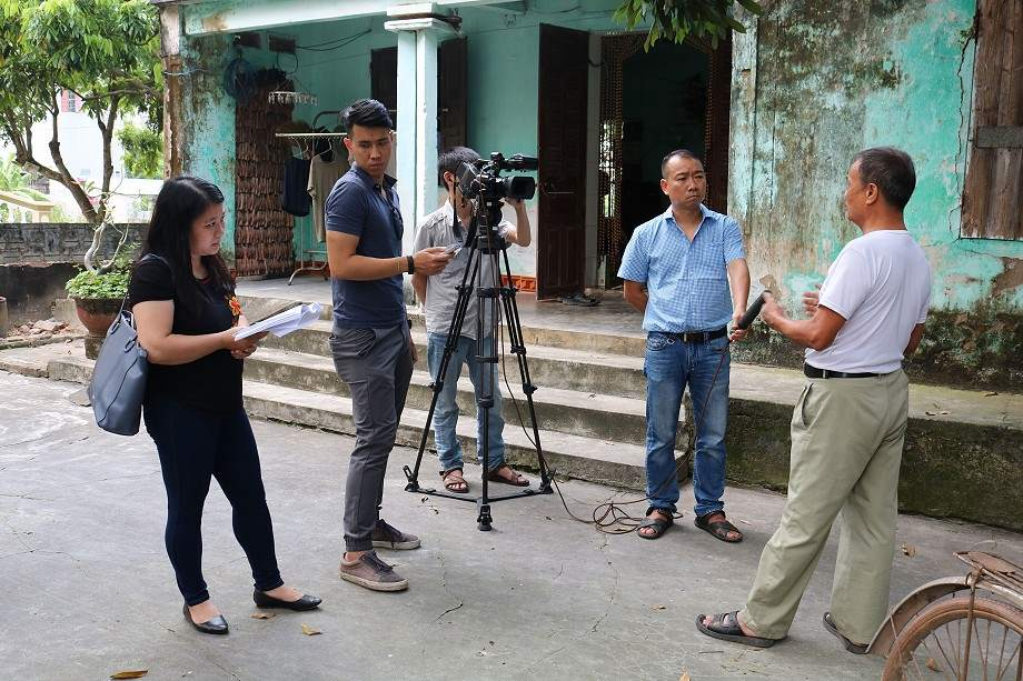 Three men and One woman standing behind a camera interviewing one man on camera